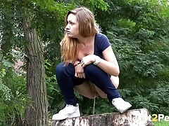 Chick pulls down her jeans and pees on a stump tubes