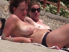 Tanning ladies go topless in the sand tubes